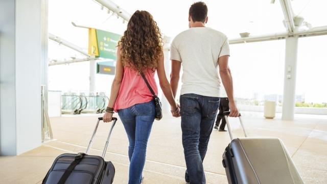 Пара в аэропорту с чемоданами